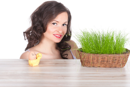 beautiful woman with easter basket with green grass, chicken and smiling egg. symbol of nature photo