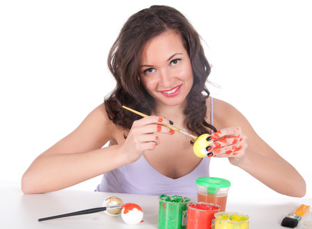 Happy young woman painting Easter eggs. Stock Photo - 23976182