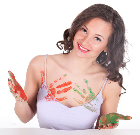 Happy young woman painting herself. photo