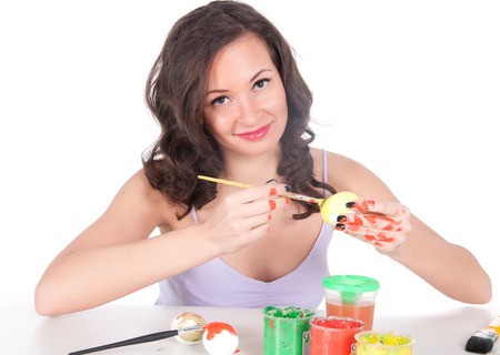 Happy young woman painting Easter eggs. Stock Photo - 23976246