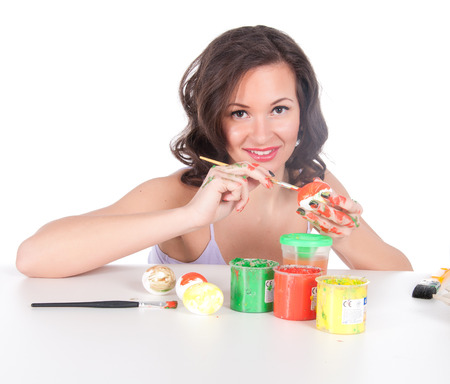 Happy young woman painting Easter eggs. Stock Photo - 23976248
