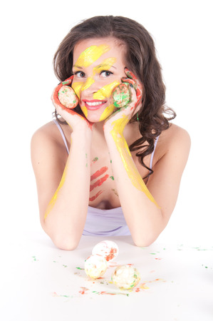 Happy young woman painting Easter eggs. photo