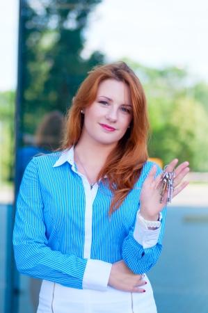 Portrait of pretty business woman with keys. photo