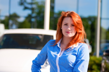 business woman with red hair in front of office building photo
