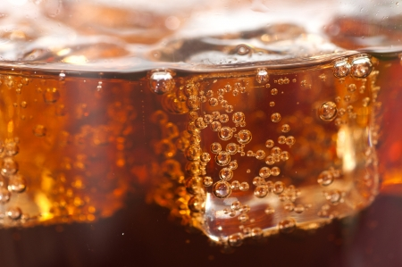 cola with ice cubes close up.