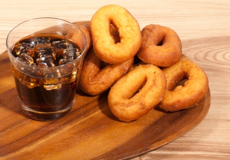 Oil donuts and cola with ice on a wooden plate. photo