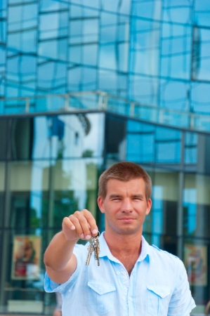 business man holding a key in front of modern business building  photo