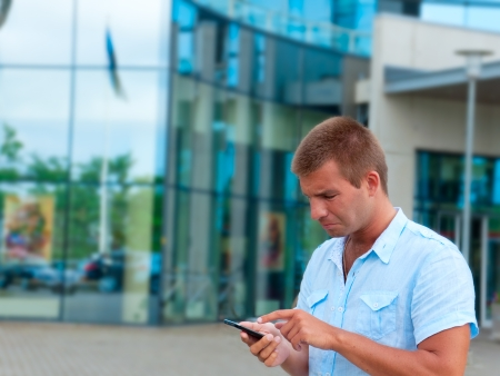 Business man speaking on phone in front of modern business building  photo