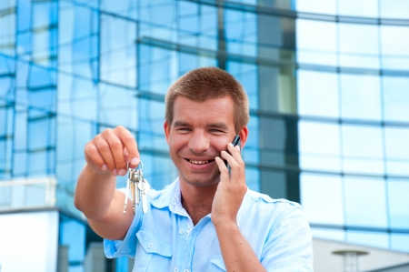 Business man speaking on phone and holding apartment key in front of modern business building. photo