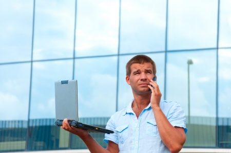 Business man with laptop and mobile phone in front of modern business building. photo