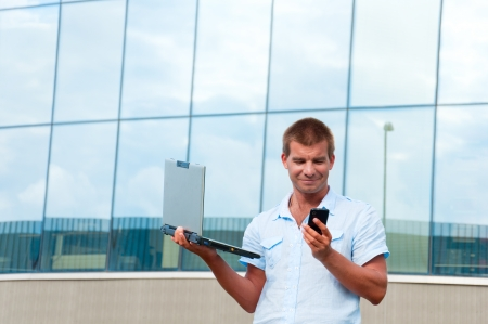 Business man with laptopand mobile phone in front of modern business building. photo