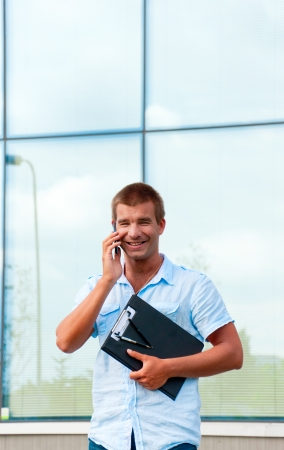 Business man with notebook and mobile phone in front of modern business building. photo