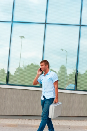 Business man with metal case and mobile phone in front of modern business building. photo