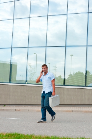 Business man with metal case and mobile phone in front of modern business building  photo