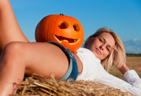 beautiful woman in jeans shorts  posing on a bale with pumpkin. photo