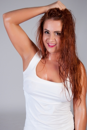 Sexy red hair woman in wet white t shirt. over grey background photo