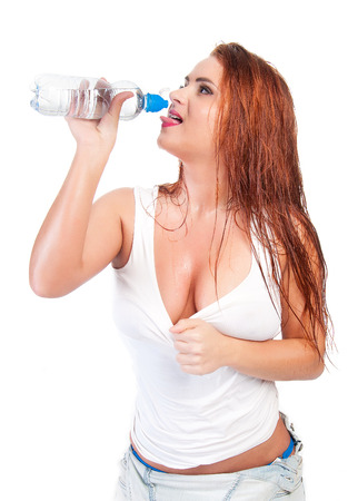 Sexy red hair woman in wet white t shirt drinking water photo