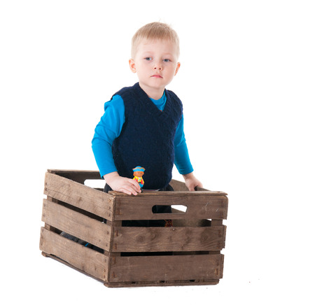 Little boy in wooden box. over white background photo