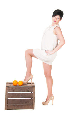 Standing woman and two oranges on a wooden box over white background  photo