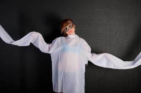 Young insane woman with straitjacket with pilot glasses over dark background photo