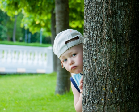 Little boywith hat  hideing behind tree. photo