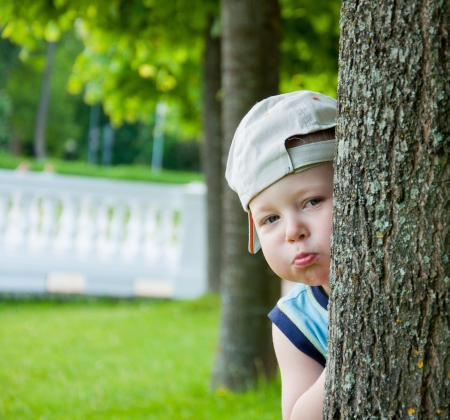 Little boy with hat  hiding behind tree. photo