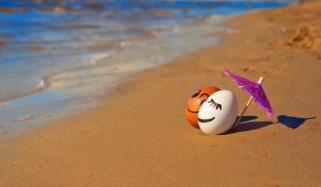 huevos de pascua divertida bajo el paraguas en una playa.