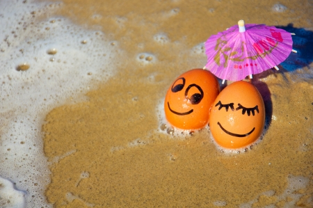 easter funny eggs under umbrella on a beach.
