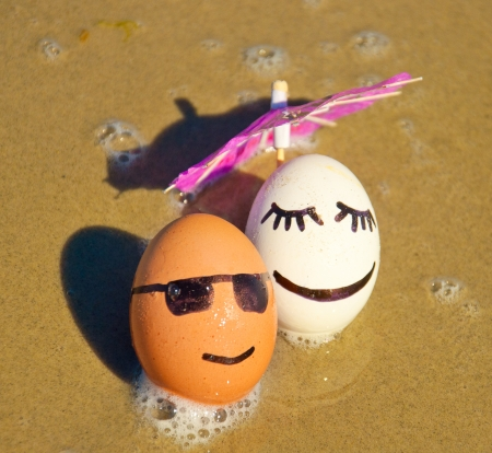 easter funny eggs under umbrella on a beach. photo