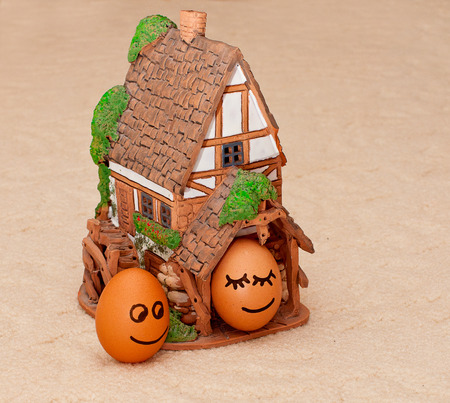 two funny smiling eggs near a house. photo