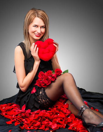 Portrait of a young beauty with rose heart. photo