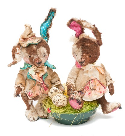 handmade old black Teddy rabbits with easter eggs and grass photo