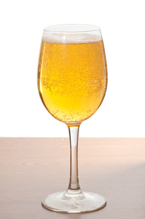 Glass of cold beer over wooden surface. photo