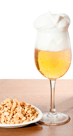 Glass of cold beer and nuts over wooden surface. photo