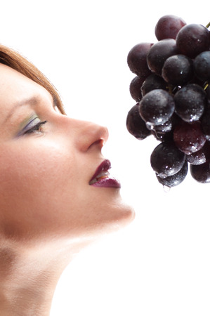 a Beautiful young woman face  with grape. photo