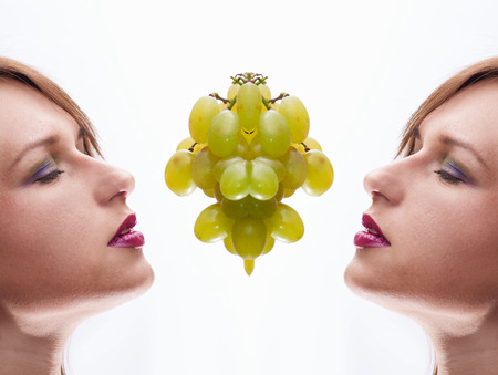 a Beautiful young woman face  with grape.