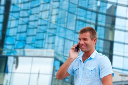 Business man speaking on phone in front of modern business building. photo