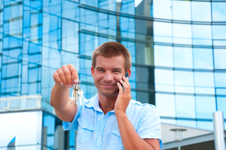 Business man speaking on phoneand holding apartament key in front of modern business building. photo