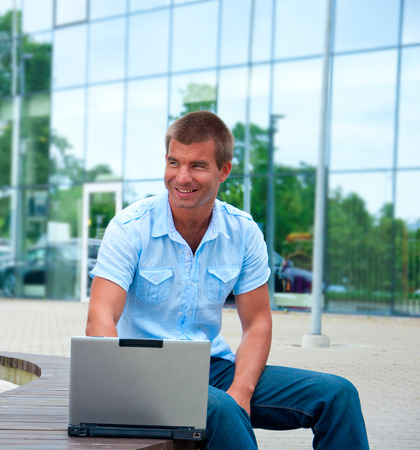 Business man with laptop in front of modern business building. photo