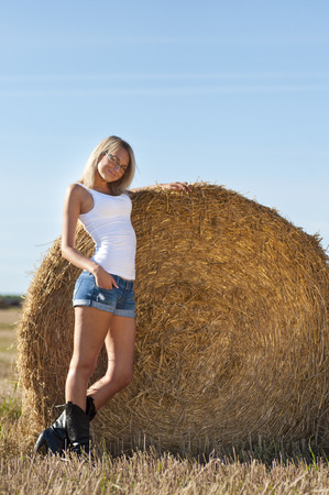 sexy woman in a jeans shorts on field. photo