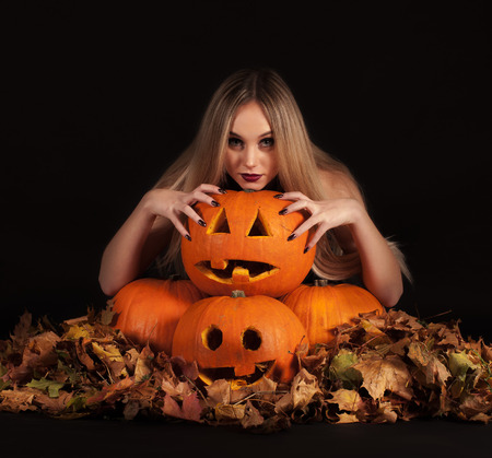 Charming halloween witch with funny pumpkins and leaves over black background photo