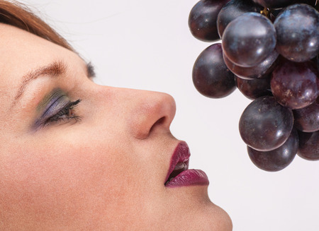 a Beautiful young woman face with grape. Stock Photo