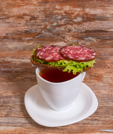 Breakfast with salami sandwich and cup of tea. photo
