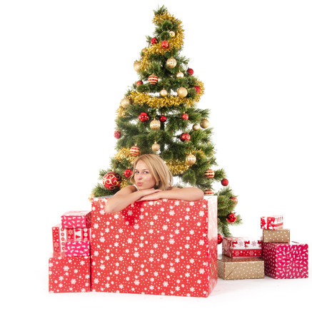 woman inside of gift box and christmas tree behind.