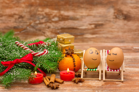 funny eggs on a beach chairs, Christmas tree, mandarine, gift and candles.  christmas background theme photo
