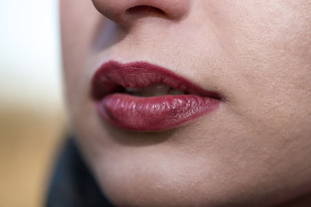 Close up detail view of a beautiful young womans mouth with perfect lips wearing glossy red lipstick outdoors. photo
