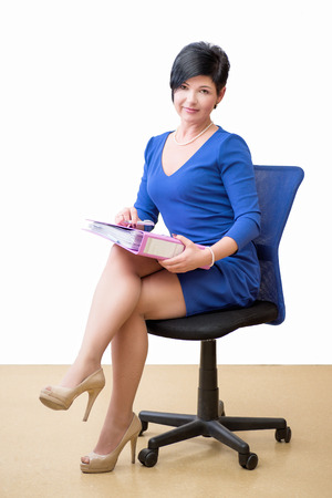 over worked: Business Woman in the office with paper sitting on a chair