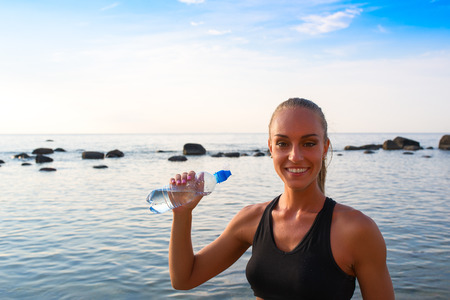 sports attire: Young blond female in sports attire rests with water.