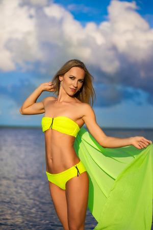 sarong: Woman at the beach holding sarong up in the air.