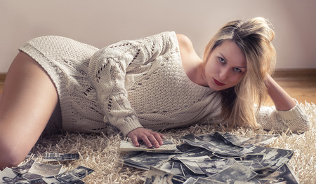 grey eyed: Young blonde woman in pajamas on white whole-floor carpet with old photos Stock Photo
